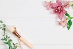 Lekmanna- sammansättning för dekorativ lägenhet med makeupprodukter och blommor Lekmanna- lägenhet, bästa sikt på vit bakgrund arkivbild