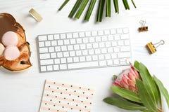 Lekmanna- sammansättning för idérik lägenhet med den tropiska blomman, makron och datortangentbordet arkivbild