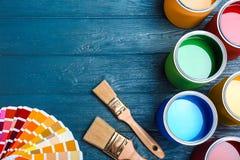Lekmanna- sammansättning för lägenhet med målarfärgcans, borstar och färgpaletten på träbakgrund royaltyfria foton
