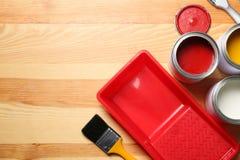 Lekmanna- sammansättning för lägenhet med målarfärgcans och borstar på träbakgrund fotografering för bildbyråer