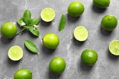 Lekmanna- sammansättning för lägenhet med nya mogna limefrukter på grå bakgrund, bästa sikt Fotografering för Bildbyråer