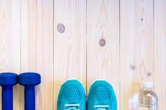 Lekmanna- skott för lägenhet av sportutrustning, skor, vatten, hörlur på träbakgrund Royaltyfria Bilder