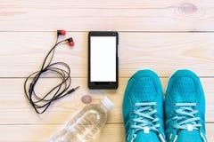 Lekmanna- skott för lägenhet av sportutrustning, skor, vatten, hörluren och telefonen på träbakgrund Royaltyfri Fotografi
