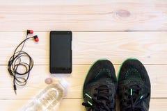 Lekmanna- skott för lägenhet av sportutrustning, skor, vatten, hörluren och telefonen på träbakgrund Royaltyfri Foto