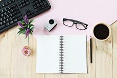 Lekmanna- stil för lägenhet av kontorsworkspaceskrivbordet med tomt anteckningsbokpapper, datortangentbordet, koppen kaffe och ti Arkivfoton