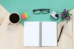 Lekmanna- stil för lägenhet av kontorsworkspaceskrivbordet med tomt den anteckningsbokpapper, koppen kaffe och tillbehör Arkivbilder