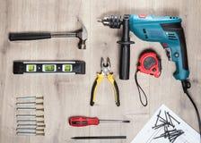 Lekmanna- uppsättning för lägenhet av konstruktionshjälpmedel som ska repareras på en träyttersida: drillborr hammare, plattång,  Arkivfoto