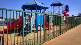 Lekplats bak stänger med blå himmel royaltyfria bilder