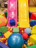 Lekplats barns glidbanor, ett lekområde av färgrika plast- bollar Gladlynta barns fritid med bollar i lekpölen, nolla royaltyfria foton