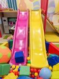 Lekplats barns glidbanor, ett lekomr?de av f?rgrika plast- bollar Gladlynta barns fritid med bollar i lekp?len, nolla royaltyfri fotografi