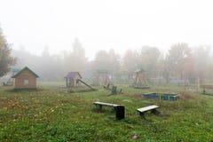 Lekplats för barn` s i lilla staden av den dimmiga morgonen för höst Royaltyfria Bilder
