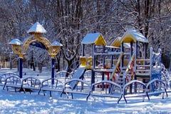 Lekplats för barn` som s täckas med snö arkivfoton