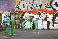 Lekplats med konditionutrustning och kaotiska grafitti Royaltyfri Bild