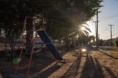 Lekplats med ljus filtrering mellan sidorna av en palmträd arkivfoto