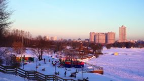Lekplats nära den djupfrysta floden Barn som spelar i vinter i den nya luften stock video