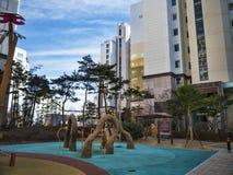 Lekplatsen för barn och stora byggnader i rikt område av den Yeosu staden royaltyfri bild