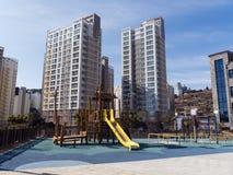 Lekplatsen för barn och stora byggnader i rikt område av den Yeosu staden fotografering för bildbyråer