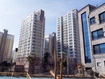 Lekplatsen för barn och stora byggnader i rikt område av den Yeosu staden arkivbilder