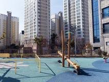 Lekplatsen för barn och stora byggnader i rikt område av den Yeosu staden royaltyfria bilder