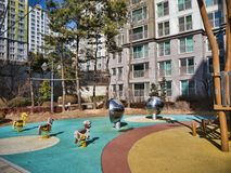 Lekplatsen för barn och stora byggnader i rikt område av den Yeosu staden royaltyfri foto