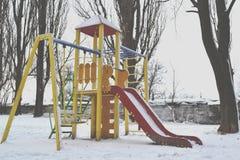 Lekplatsen i vintern parkerar Filialerna av gran-trädet som täckas av snö Arkivbild