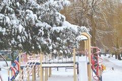 Lekplatsen i vintern parkerar Filialerna av gran-trädet som täckas av snö Arkivfoto
