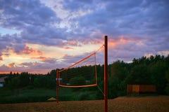 Lekplatsen med strandvolleyboll förtjänar under solnedgånghimlen royaltyfri fotografi