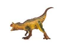 Leksak för carnotaurus för brunt för sidosikt på vit bakgrund Royaltyfri Fotografi