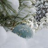 Leksak för nytt år på bakgrunden av träd som täckas med snökopieringsutrymme arkivfoto