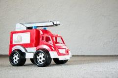 Leksak f?r barn` s R?d bil Gammal plast- brandlastbil fotografering för bildbyråer