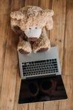Leksak och bärbar dator för nallebjörn på golv Royaltyfria Foton
