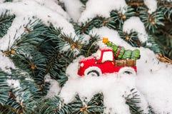 Leksakbil med julgranen på snöig filialgran arkivbild