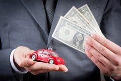 Leksakbil och dollar i händerna av begreppet för affärsman för försäkring, köpande, hyra, bränsle eller service och reparationskos Royaltyfri Bild