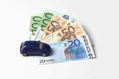 Leksakbil och fläktade euroanmärkningar på vit bakgrund Royaltyfri Foto