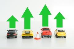 Leksakbilar modellerar med gröna pilar som föreslår bilindustritillväxt Arkivbilder