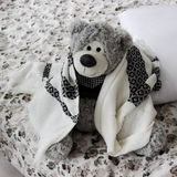 Leksakbjörnen sitter på en säng som är hoprullad i en pläd Royaltyfri Foto