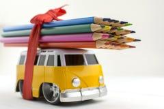 Leksakbussen bär en grupp av kulöra blyertspennor på taket Fokus på blyertspennaspetsar arkivfoton