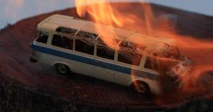 Leksakbussen smälter under en ström av brandslutet upp stock video