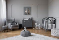 Leksaken på grå puff i mitt av moderiktigt behandla som ett barn sovrummet med den gråa trävaggan, byrån och den bekväma fåtöljen arkivfoton