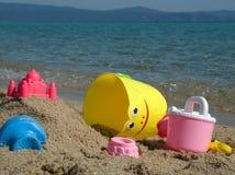 Leksaker för barn` s i sanden på kusten Arkivfoto