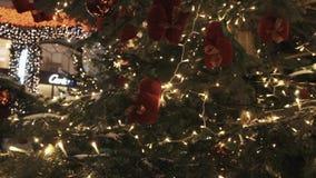 Leksaker för röd ekorre och girland för vitt ljus på julträd utomhus arkivfilmer