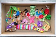 Leksaker och dockor som göras från den färgrika vävstolen, sätter band royaltyfria foton