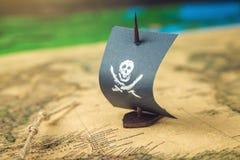 Leksakfartyget piratkopierar flaggaskallen och ben på världskartan av de handgjorda brädelekarna för spelplanen Fotografering för Bildbyråer