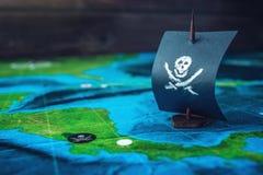 Leksakfartyget piratkopierar flaggaskallen och ben på världskartan av de handgjorda brädelekarna för spelplanen Royaltyfri Foto