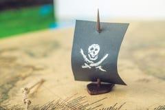 Leksakfartyget piratkopierar flaggaskallen och ben på världskartan av de handgjorda brädelekarna för spelplanen Royaltyfri Fotografi