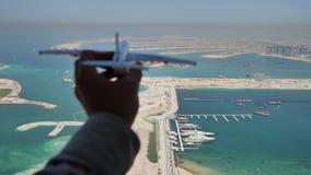 Leksakflygplan flyger mot bakgrunden av Palm Jumeirah ön i Dubai Begreppet av loppet lager videofilmer
