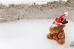 Leksakhjortar på en snöig träbakgrund Arkivfoto