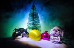 Leksakhund - ett symbol av det nya året under snön mot bakgrunden av gran förgrena sig Leksaks hund som ett symbol av 2018 nya år Arkivfoto