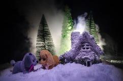 Leksakhund - ett symbol av det nya året under snön mot bakgrunden av gran förgrena sig Leksaks hund som ett symbol av 2018 nya år Fotografering för Bildbyråer