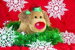 leksakhund för nytt år som omges av dekorativa julbeståndsdelar och granfilialer på röd bakgrund Royaltyfria Bilder